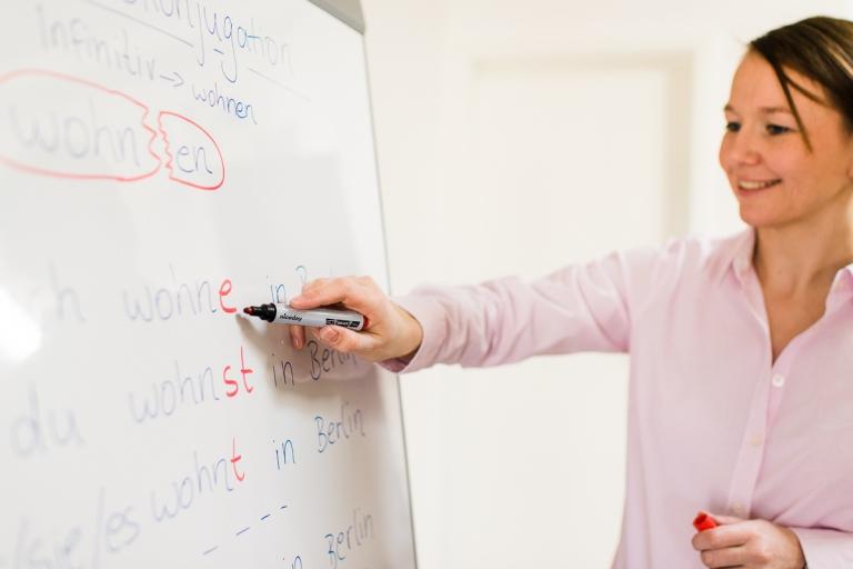 Sprachlehrerin zeigt auf Tafel