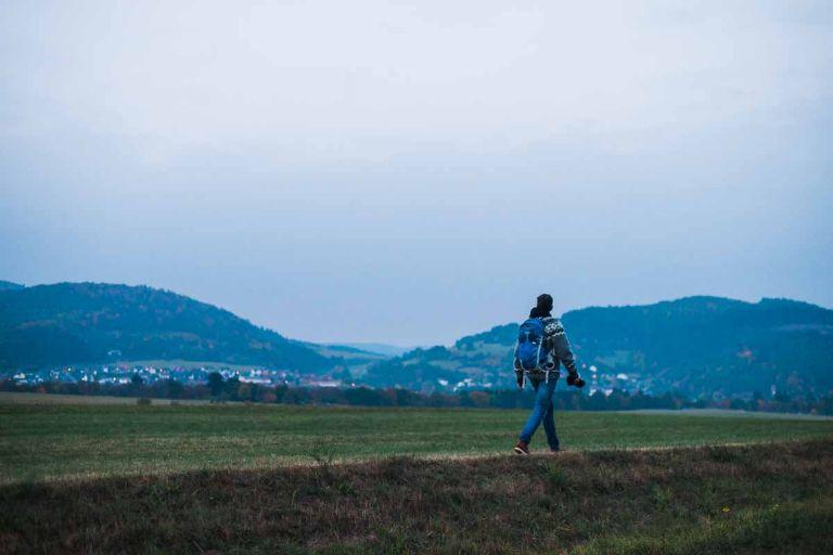 Willi Weitzel geht in der Dämmerung auf einem Feld an einem Dorf vorbei.